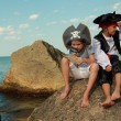Boy and girl in a pirate costume with a map and a magnifying glass sitting on a large rock by the sea — Стоковая фотография