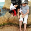 Boy and girl in a pirate costume with a map and a magnifying glass sitting on a large rock by the sea — ストック写真