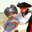 Beautiful little boy and girl dressed in pirate costumes and holding starfish on the beach — Stock Photo