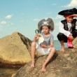 Boy and girl in a pirate costume with a map and a magnifying glass sitting on a large rock by the sea — Stockfoto