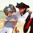 Cute little boy in a pirate costume and a little girl in a hat with a skeleton — Stock Photo