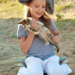 Cute little girl in a pirate hat holding little kitten in nature — Stock Photo