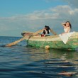 Beautiful smiling young boy and girl as a pirate and a lady swimming in the old small boat — Stock Photo #29239863