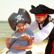 Cute little boy in a pirate costume and a little girl in a hat with a skeleton symbol of piracy  — Stock Photo