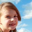 Portrait of cute smiling little girl on a background of blue sky with clouds outdoors — Stock Photo #29239935