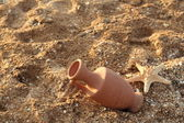 Amphora in the sand washed by sea water — Stock Photo