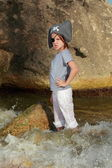 Encantadora chica joven en un pirata sombrero de pie en el agua en la playa en verano — Foto de Stock