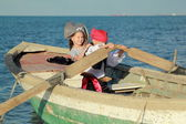 Joyful young children playing pirates in the old dirty boat in the sea — Stock Photo