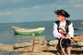 Handsome Boy dressed as a pirate on the sea coast — Stock Photo