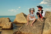 Boy and girl in a pirate costume with a map and a magnifying glass — Stock Photo