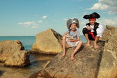 Beautiful young kids pirate boy and girl holding a pirate map and a magnifying glass — 图库照片
