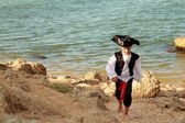 Charming young pirate boy in a red bandanna standing against the background of blue sea — Stock Photo