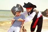 Milý chlapeček v pirát kostým a malá holčička v klobouku s kostrou — Stock fotografie