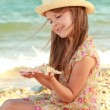 Caucasian cute young girl in a summer dress and hat holding a starfish. — Stock Photo #29241369