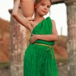 Caucasian smiling little girl in a bright emerald green dress standing in the ruins of the ancient city of Pantikapaion — Stock Photo