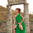 Caucasian smiling little girl in a bright emerald green dress standing in the ruins of the ancient city of Pantikapaion. — Stock Photo #29241773