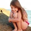 Cute little girl in a bathing suit sitting on a large rock by the sea. — Stock Photo #29242523