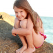 Cute little girl in a bathing suit sitting on a large rock by the sea. — Stock Photo #29242525