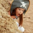 Pretty emotional girl dressed as a pirate on the beach looking for treasure. — Stock Photo