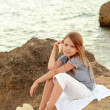 Sweet girl with long healthy hair in casual clothes on the bank of the summer sea — Foto Stock
