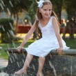 Thoughtful little casual girl standing near city fountain — Stock Photo #29244917