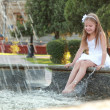 Cheerful cute little girl in white dress sitting near the fountain — Stock Photo #29244953