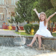 Cheerful cute little girl in white dress sitting near the fountain and smiling at summer theme — Stock Photo #29244963