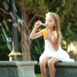 Smiling happy little girl in white dress enjoying cool water in a fountain — Zdjęcie stockowe