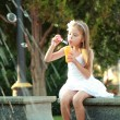 Little girl playing and having fun enjoying the spray of the fountain on a hot day outdoors — Stock Photo