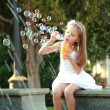 Little girl having fun playing and enjoying the spray of the fountain on a hot day — Stock Photo