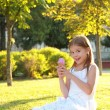 Cute little girl is blowing a soap bubbles. — Foto Stock