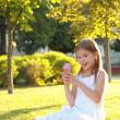 Cute little girl is blowing a soap bubbles. — Photo