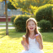 Contented smiling little girl is holding two ice creams sitting on the grass — Foto Stock