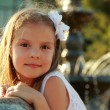 Adorable cute little girl smiling and posing near the fountain — Stock Photo #29245499
