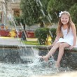 Cheerful cute little girl in white dress sitting near the fountain and smiling at summer theme — Stock Photo #29245569