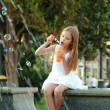 Cute smiling young girl in a beautiful white dress flounder feet in the fountain  — Stock Photo