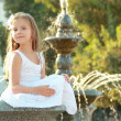 Adorable cute little girl smiling and posing near the fountain in the summer outdoors — Stock Photo