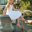 Adorable cute little girl smiling and posing near the fountain in the summer outdoors — Stock Photo #29245949