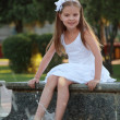 Cheerful cute little girl in white dress sitting near the fountain and smiling at summer theme — Stock Photo #29245965