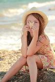 улыбаясь молодая девушка держит морская звезда, сидя на берегу моря летом. — Стоковое фото