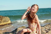 Adorable happy little girl holding a seashell on the sea beach on a sunny day. — Stock Photo