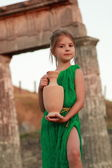 Joyful smiling girl in a beautiful emerald green dress with an amphora in the role of the Greek goddess. — Stock Photo