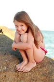 Cute little girl in a bathing suit sitting on a large rock by the sea. — Zdjęcie stockowe