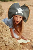 Cute young girl in a pirate hat with a pirate map in hand on a background. — Stock Photo
