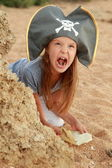 Emotional young girl in a pirate hat is angry and looking for treasure on the beach. — Stock Photo