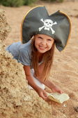 Cute young girl in a pirate hat with a pirate map in hand on a background of sea sand. — Stock Photo