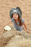 Cute young girl in a pirate hat with a pirate map in hand. — Stock Photo