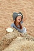 Cute young girl in a pirate hat with a pirate map in hand on a background of sea sand on the beach. — Stock Photo