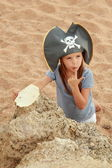 Emotional young girl in a pirate hat is angry and looking for treasure on the beach in the hot summer day. — Stock Photo