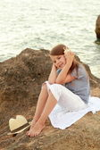 Happy cute little girl with a beautiful smile is sitting on the beach in the evening. — Stock Photo